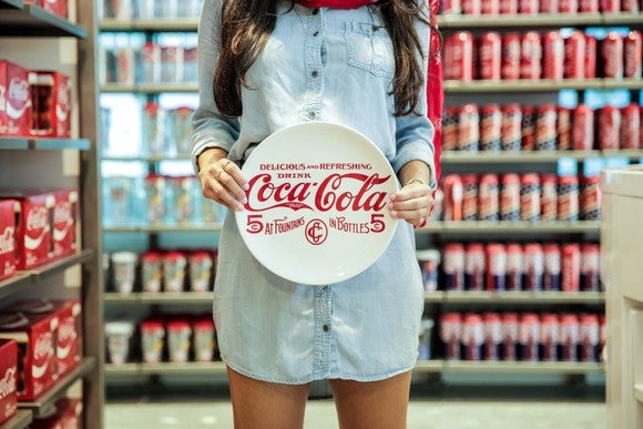 A woman holds a plate with the Coca-Cola logo.
