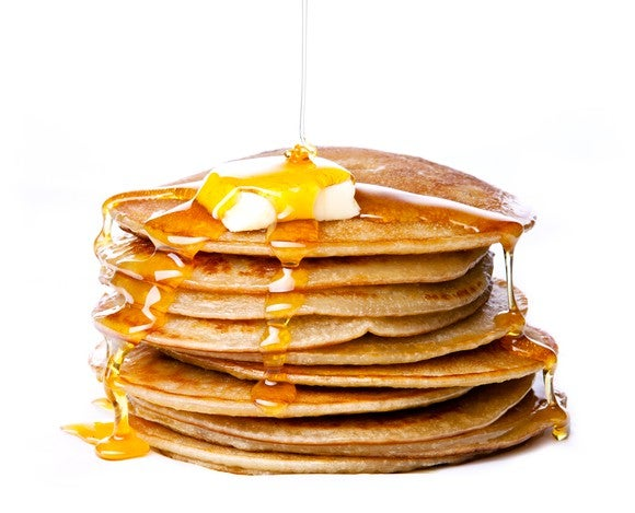 Pancakes with syrup drizzling over it.