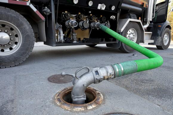 Fuel tanker truck delivering gasoline to a gas station.