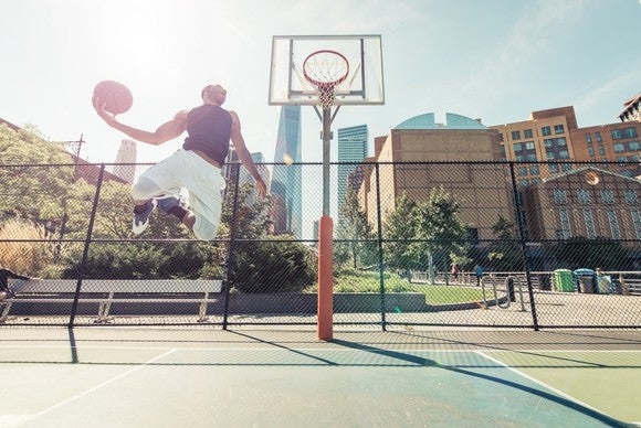 Man performs a slam dunk on a basketball court.