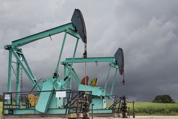 Two green oil wells sitting under a stormy grey sky.