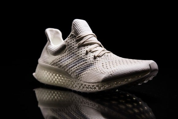 One of Adidas' new, futuristic sneakers against a black background.