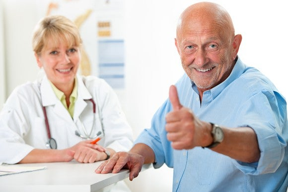 A man sits at a desk with his doctor, looking happy and giving a thumbs-up sign.