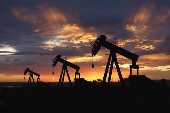 Three oil pumps at sunset.