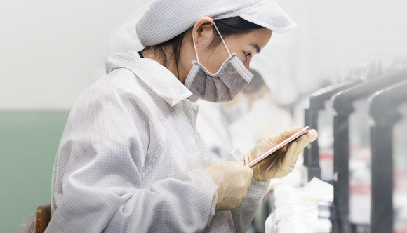 A worker performing a quality inspection on an iPhone