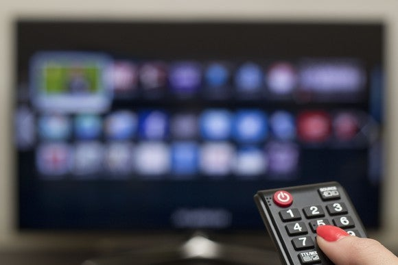 A hand holding a cable remote points it at a TV.