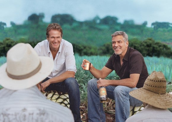 George Clooney and business partner sitting at the edge of an agave field in Mexico, enjoying a batch of tequila with farm workers.