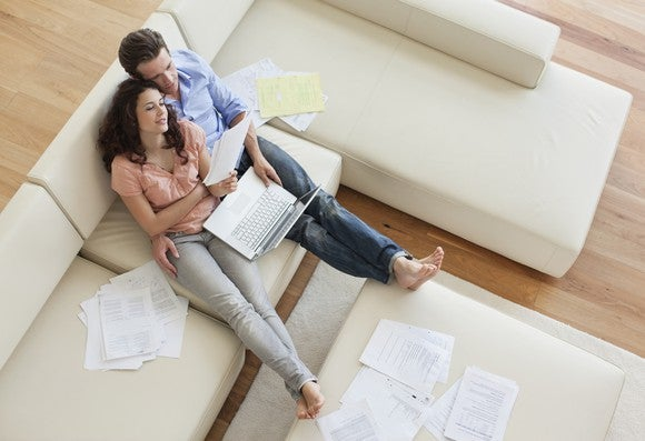 Couple on sofa looking at documents and PC