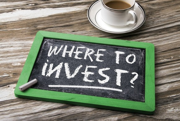"Slate on table next to coffee cup with ""where to invest"" written in chalk."