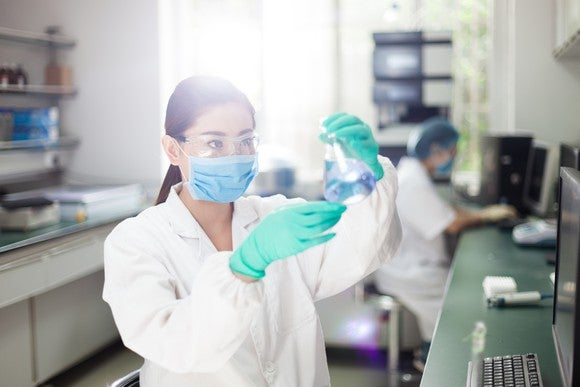 Pharmaceutical laboratory scientist examining a flask.