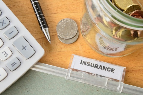 "A folder labeled ""insurance"" sits on a desk, along with coins, a pen, and a calculator."