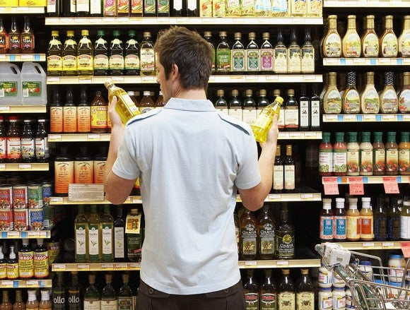 A young shopper in a grocery store compares two similar products.