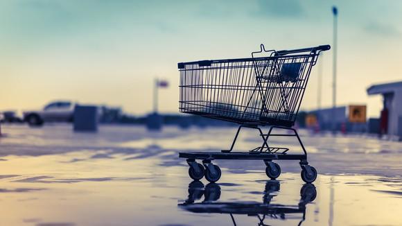 An empty shopping cart in an empty parking lot.
