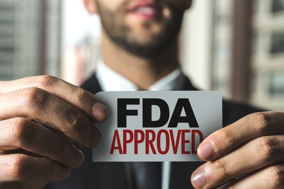 "A man holding a sign that reads ""FDA Approved."""