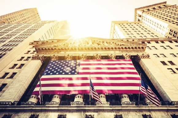 The exterior of the New York Stock Exchange, looking up at a display of American flags.