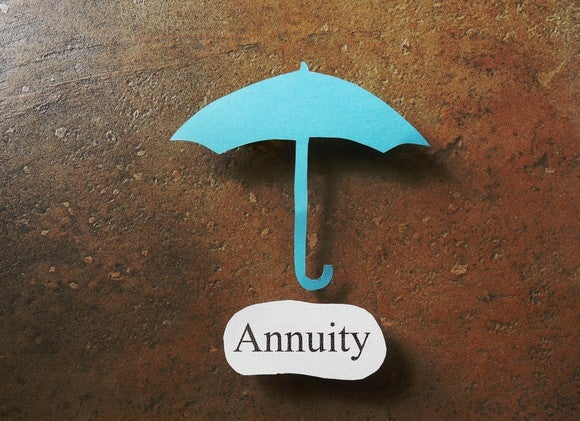 "A blue cutout of an umbrella hovers over the word ""annuity."""