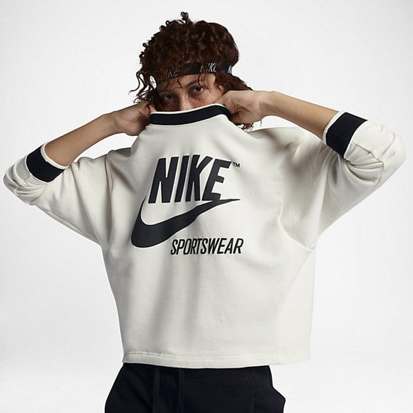 A model pulls a Nike sweatshirt over her face.