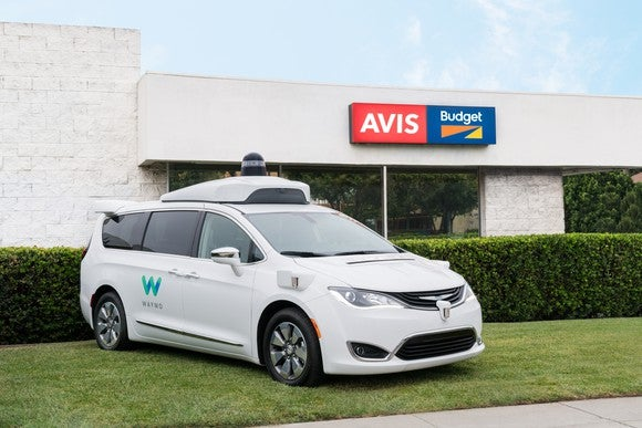 A Waymo vehicle in front of a building bearing the Avis/Budget logo.
