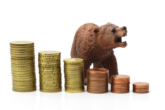 A growling bear stands behind progressively smaller stacks of coins.