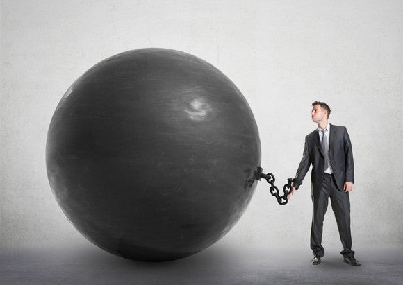 A man in a suit, chained to giant black ball.