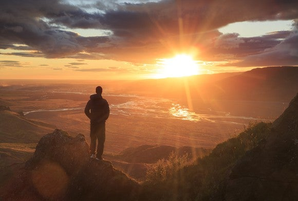 From a mountaintop, a man looks out at the sun on the horizon.
