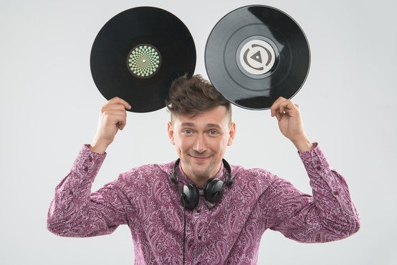 excited young DJ with stylish haircut, bow tie having fun with vinyl records - holding two up to his head like Mickey Mouse ears