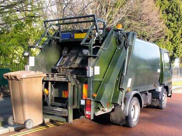 A garbage truck picking up bins.