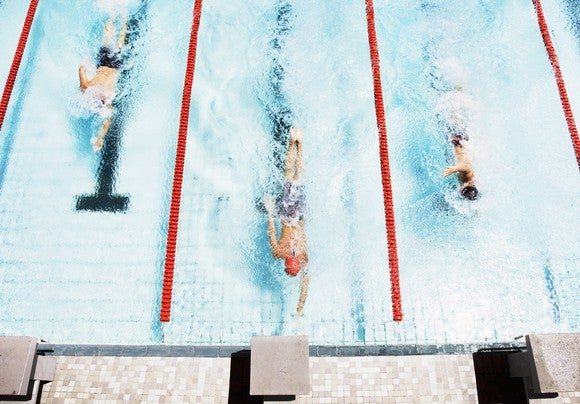 Three swimmers in a race, coming to ledge of pool
