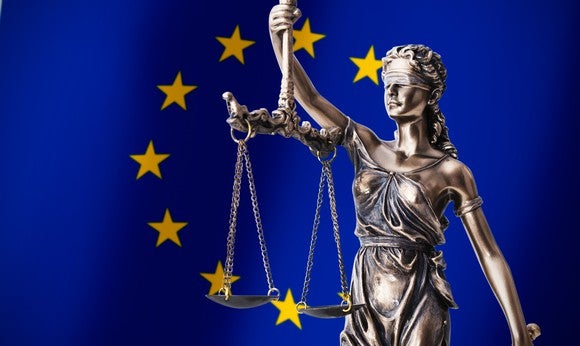 Lady Justice statue (blindfolded woman holding balance scales) with the flag of Europe as a backdrop.