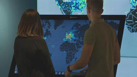 Two people looking at a global map demonstrating Microsoft's cloud reach.