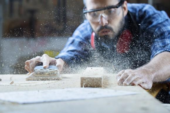Carpenter blowing sawdust off wood