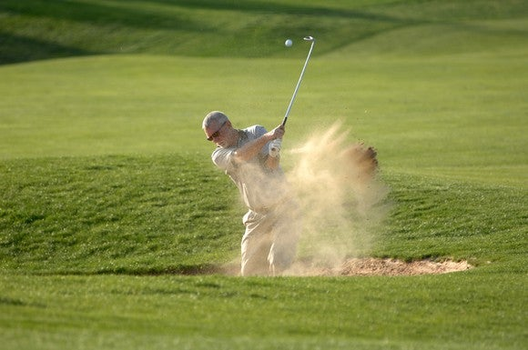 Man golfing in sand trap