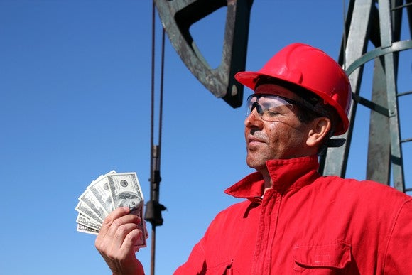 A rig worker holding cash.