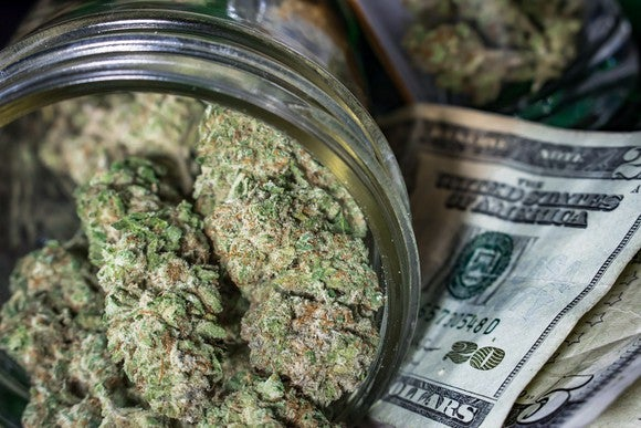 Cannabis buds in a jar atop a pile of cash.