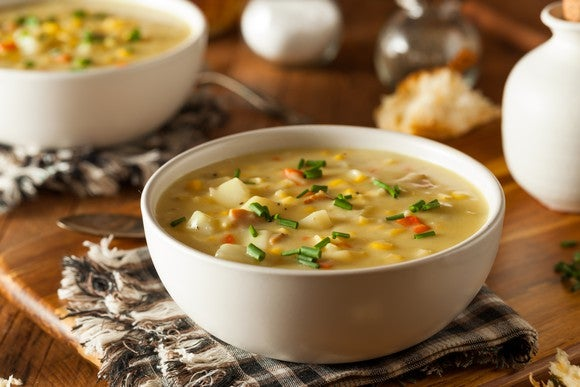 A bowl of corn chowder sits on a dinner table.