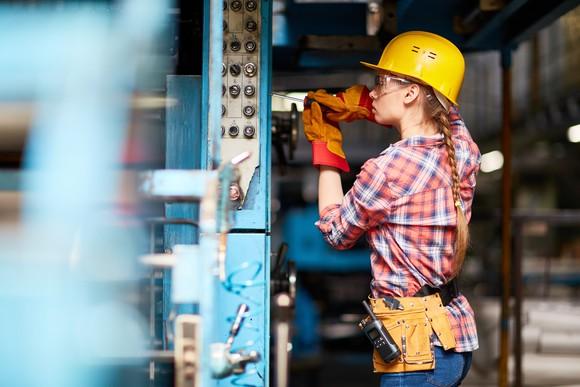 A maintenance worker fixes a machine