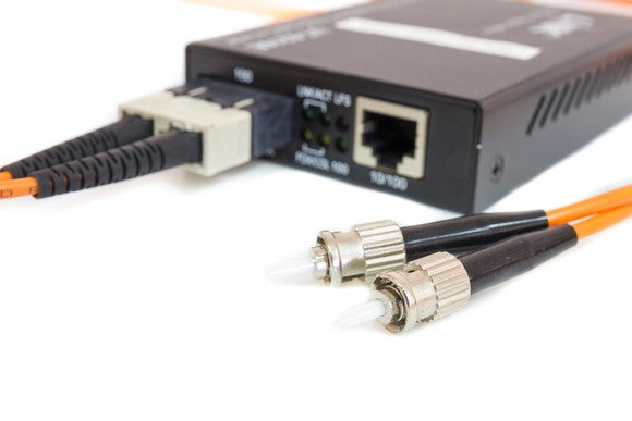 Fiber-optic cables connected to transceivers in an Ethernet media conversion box.