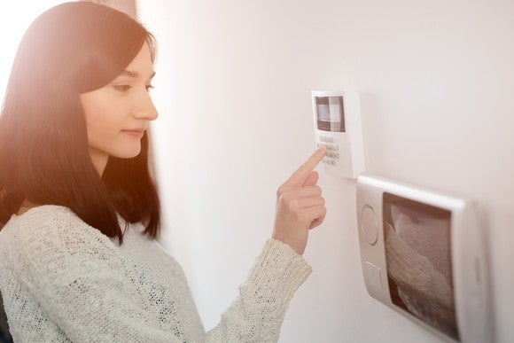 Woman entering a code on home security panel