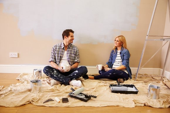 Couple sitting on the floor while painting