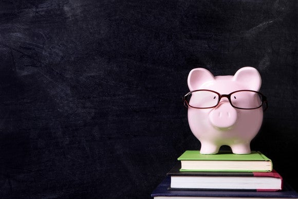 A piggybank wearing glasses and sitting on a few books.