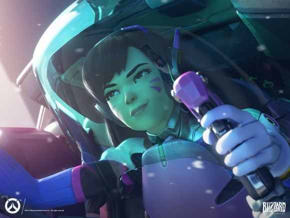 """An """"Overwatch"""" character sitting inside a tank outfit with her hands holding a joystick, and an intense look on her face."""