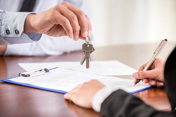 Closing attorney handing keys to house.