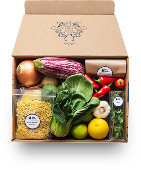 A Blue Apron delivery box containing noodles, vegetables, and fruit.