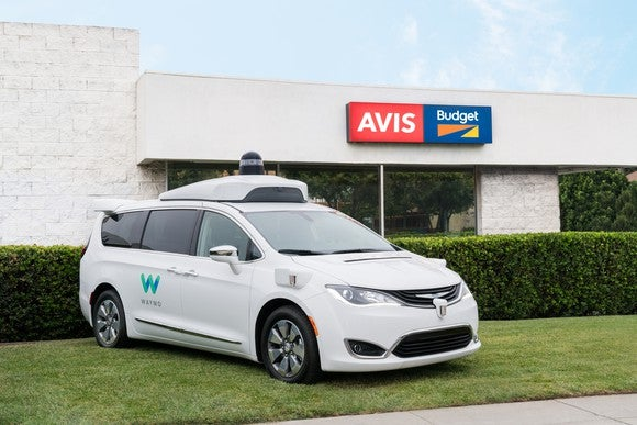 A Chrysler Pacifica minivan outfitted with Waymo self-drive technology is parked in front of an Avis Budget location.
