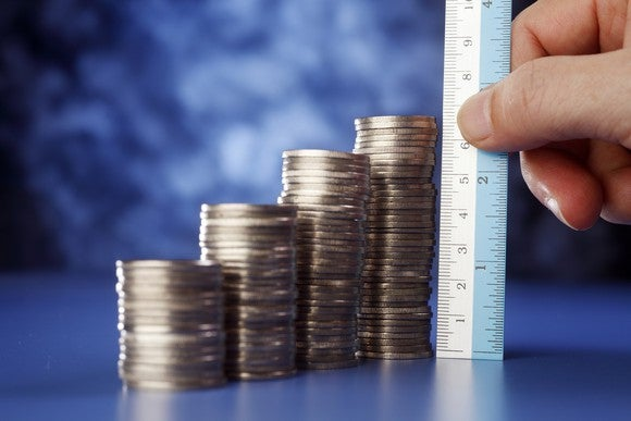 A hand holds a ruler, measuring stacks of coins growing progressively taller.