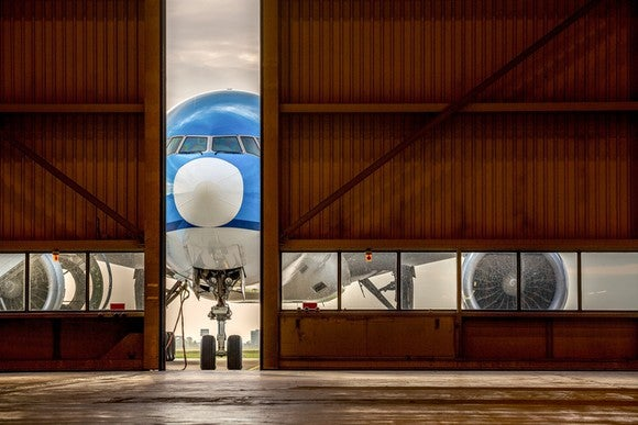Blue plane in front of half-open hangar door, waiting to enter.