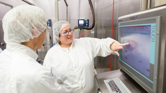 Prescription drug manufacturing employees at Johnson & Johnson pointing to a digital screen.