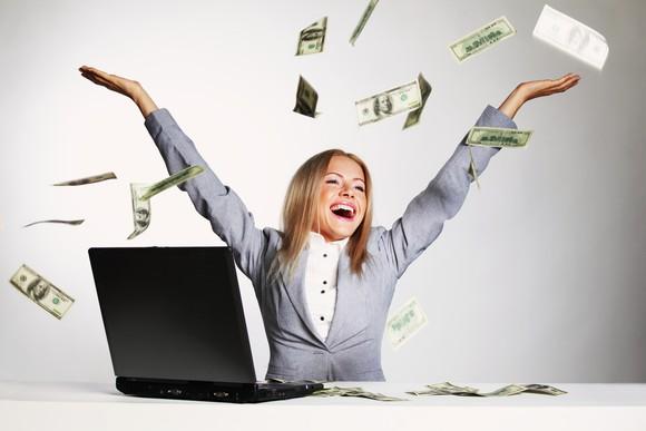 Businesswoman celebrating in a shower of hundred-dollar bills.