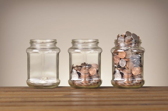 Three jars are lined up on a table, filled with increasingly larger amounts of coins.