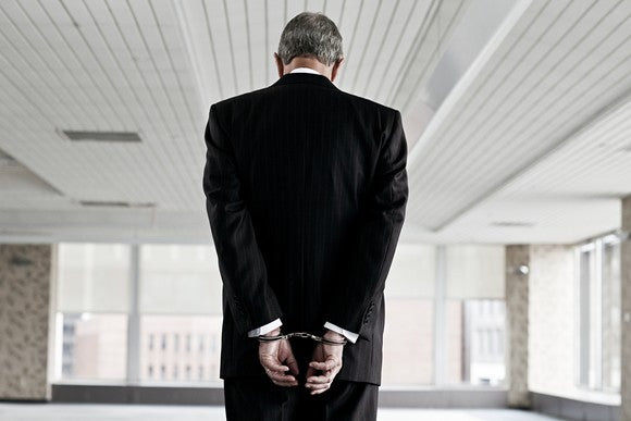 A businessman in handcuffs.